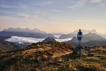 ein auf einem Felsvorsprung stehender Mann blickt auf die entfernten, wolkenumhangengen Berggipfel