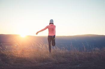 eine Läuferin dehnt sich, während im Hintergrund die Sonne aufgeht