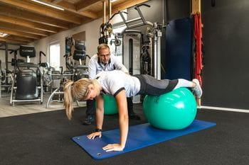 Eine junge Dame bei einer Liegestütz Übung unterstützt von Gernot Schweizer