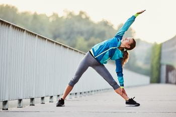 a runner is stretching while standing on concrete