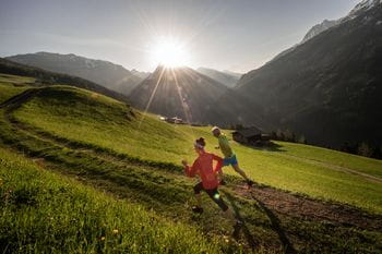 two people are sprinting along a mountain path