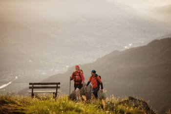 Hikers next to a bench with view on the valley