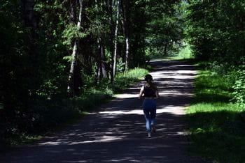 A women runs through a shadowy avenue