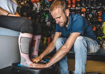 Ein Kunde beim Anpassen der Skischuhe: Der Mitarbeiter macht Fußabdrücke von den Füßen in Skisocken für Einlagen für die Skischuhe.