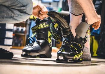 Ein Kunde beim Anpassen der Skischuhe: Der Einstieg in einen Skischuh mit der Hilfe eines Verkäufers, der den Skischuh weit auseinander drückt.