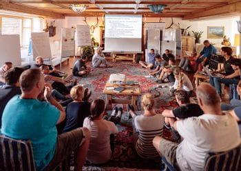 mehrere Personen sitzen dicht gedränkt in einem Raum, um sich eine Präsentation anzusehen