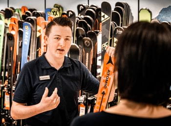 Bründl Sports employee explains everything about an Atomic ski to a consumer