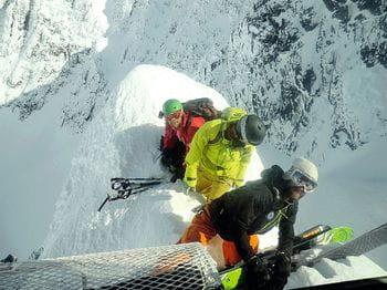Drei Männer beim Skiausladen aus einem Helikopter – auf einem schmalen Grat
