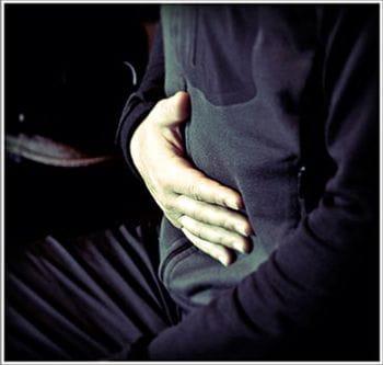 eine Person hält ihre Hand auf ihren Bauch