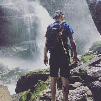 Ein Wanderer steht in der Gischt eines Wasserfalls.