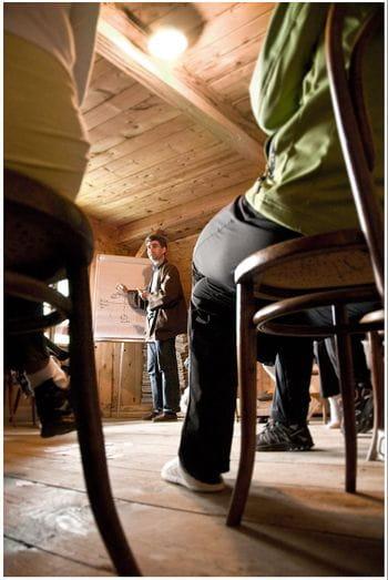 das Bild zeigt zwei Stühle von Zusehern eines Vortrages, im Hintergrund erkennt man eine stehende Person, die gerade den Vortrag hält