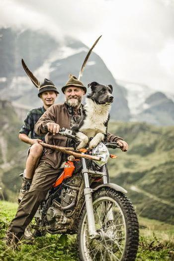 Ein Mann, ein junger Mann und ein Hund fahren auf dem Motorrad über die Wiesen