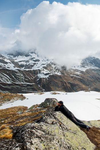 A man takes a picture in the mountains