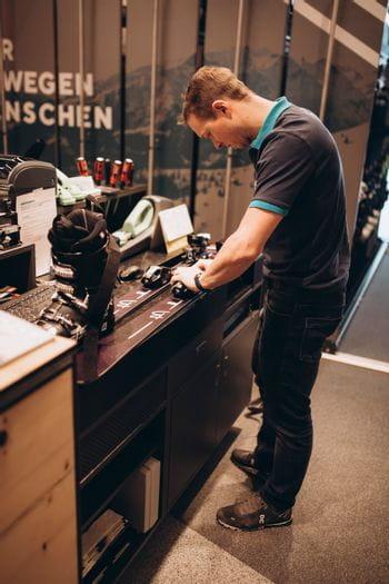 Ein Mitarbeiter aus dem Bründl Sports Skiverleih beim Einstellen der Bindung