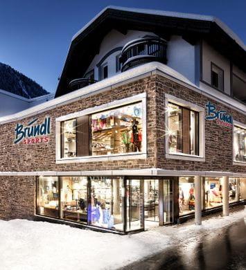 Bründl Sports Ischgl Zentrum well-lit shopwindow - winter evening view <br/>
