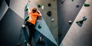 Young boy with an orange shirt while bouldering at the Bründl Sports shop in Saalfelden