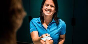 Junge Dame übergibt die Kundenkarte von Bründl Sports an den Kunden