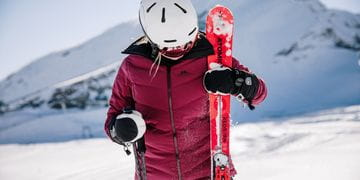 A female skier stands in the snow, her skis in one hand and her poles in the other hand