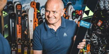 Manfred Rogetzer, Leiter Bründl Sports Racing Service, mit Fischer Ski vor einer Skiwand
