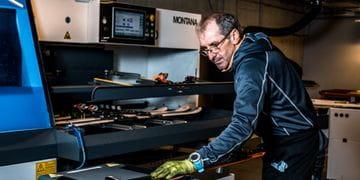 Ein Mitarbeiter präperiert einen Ski an einer großen Maschine