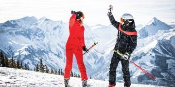 Skifahrer auf der Schmittenhöhe die sich einklatschen mit dem Kitzsteinhorn im Hintergrund