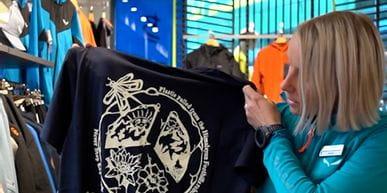 Bründl Sports Mitarbeiterin steht in einem Geschäft und stellt ein T-Shirt aus recycelten Himalaya Plastikflaschen vor.