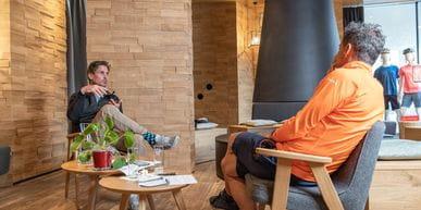 Gespräch sitzend zwischen zwei Personen neben zwei kleinen Tischen