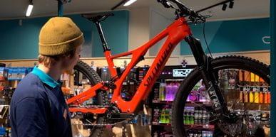 Bründl Sports Mitarbeiter steht in einem Geschäft und stellt ein rotes Fahrrad von Specialized vor.