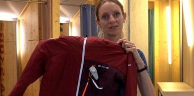 Bründl Sports Mitarbeiterin steht im Geschäft und stellt eine Ortovox Wanderjacke vor.