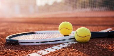 Ein Tennisschläger mit zwei Tennisbällen