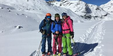 Three skiers at the snowy Alps
