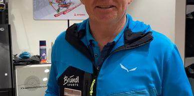Bründl Sports Mitarbeiter mit einem Skischuh in der Hand vor der Wand