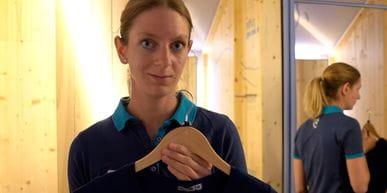 Bründl Sports Mitarbeiterin steht in einem Geschäft und präsentiert ein Funktionsshirt aus Algen.