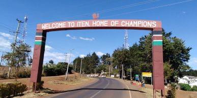 """Ein Torbogen über einer Straße mit der Aufschrift """"Welcome to Iten. Home of Champions"""""""