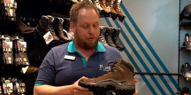 Bründl Sports Mitarbeiter steht vor einer Schuhwand und stellt den Lowa Renegade Wanderschuh vor.