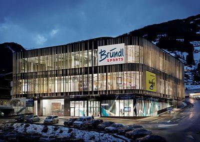 Der Bründl Sports Shop direkt an der Spieljochbahn hell erleuchtet in der Winterdämmerung