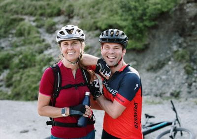 A female and a male cyclists smile into the camera wearing their mountainbike gear