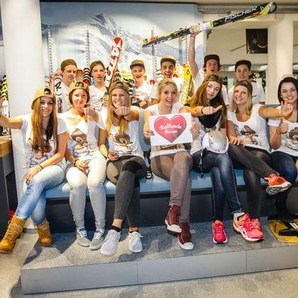 """eine Gruppe jugendlicher Lehrlinge hält ein Plakat mit dem Titel """"Rollende Herzen"""" in die Kamera"""