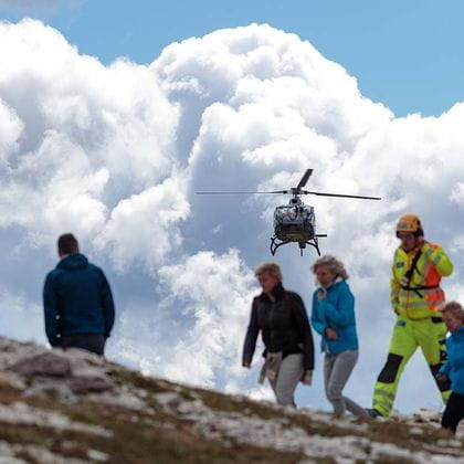 a helicopter flies over several people on a mountain