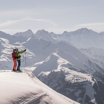 two skiers are standing in the snow and are looking at the distant mountains