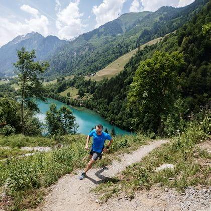 Ein Läufer läuft einen Berg hinauf, im hintergrund ein gletscherblauer Bergsee.
