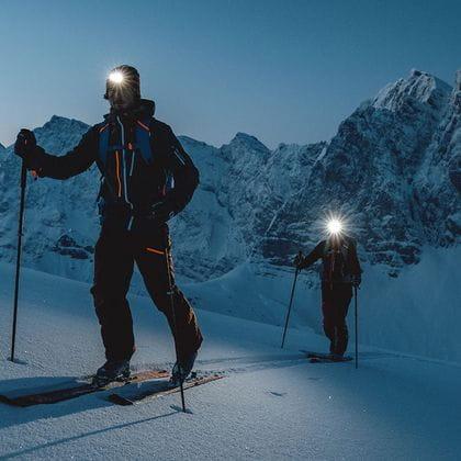 A couple ski touring at night.