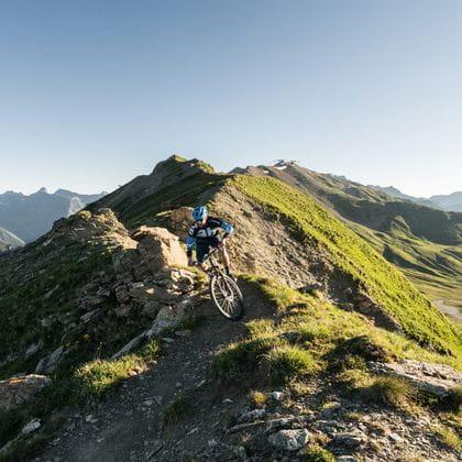 ein Mountainbiker fährt über ein Grat in den Bergen