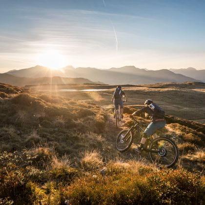 zwei Biker durchqueren eine Wiesenlandschaft in den Bergen