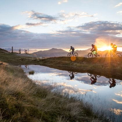 three mountain bikers are crossing grasslands in the alps, their silhouettes and the blue, bloudy evening sky are mirrored by a small stretch of water lying in front of them