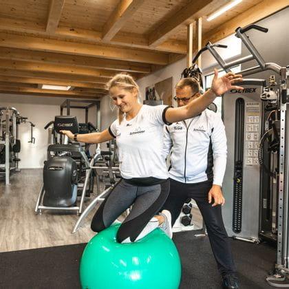 Eine junge Dame bei einer Übung am Pezziball unterstützt von Gernot Schweizer