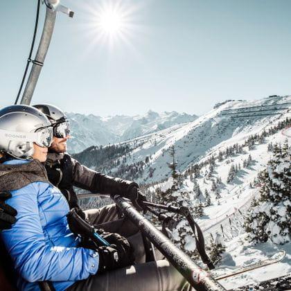 zwei Skifahrer im Sessellift