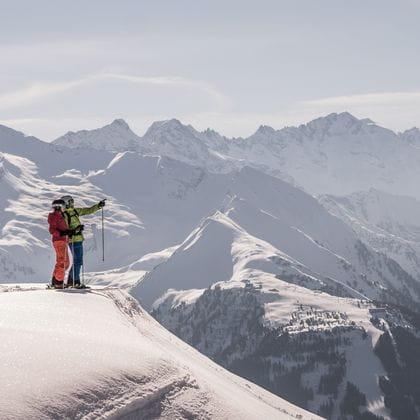 zwei Skifahrer stehen auf einem Vorsprung und blicken in die Ferne