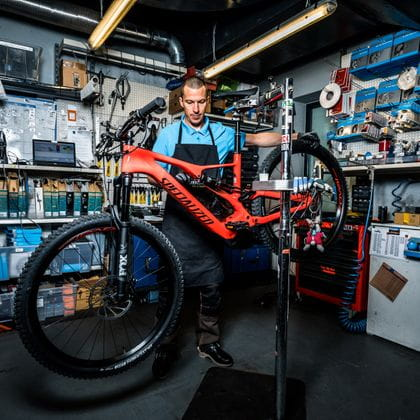 A staff member with a bike in the bicycle repair shop