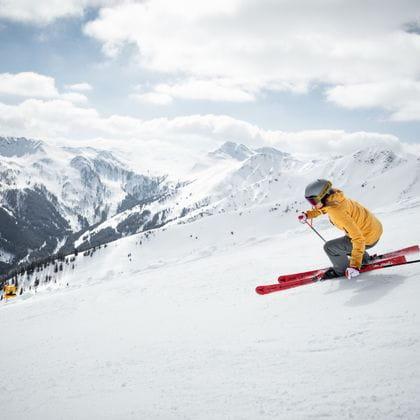 eine Frau fährt auf einer Skipiste mit Leihski von Bründl Sports